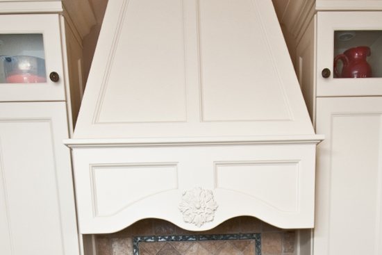 Custom CNC range hood, custom base corbels around glass cook top and solid surface counter top